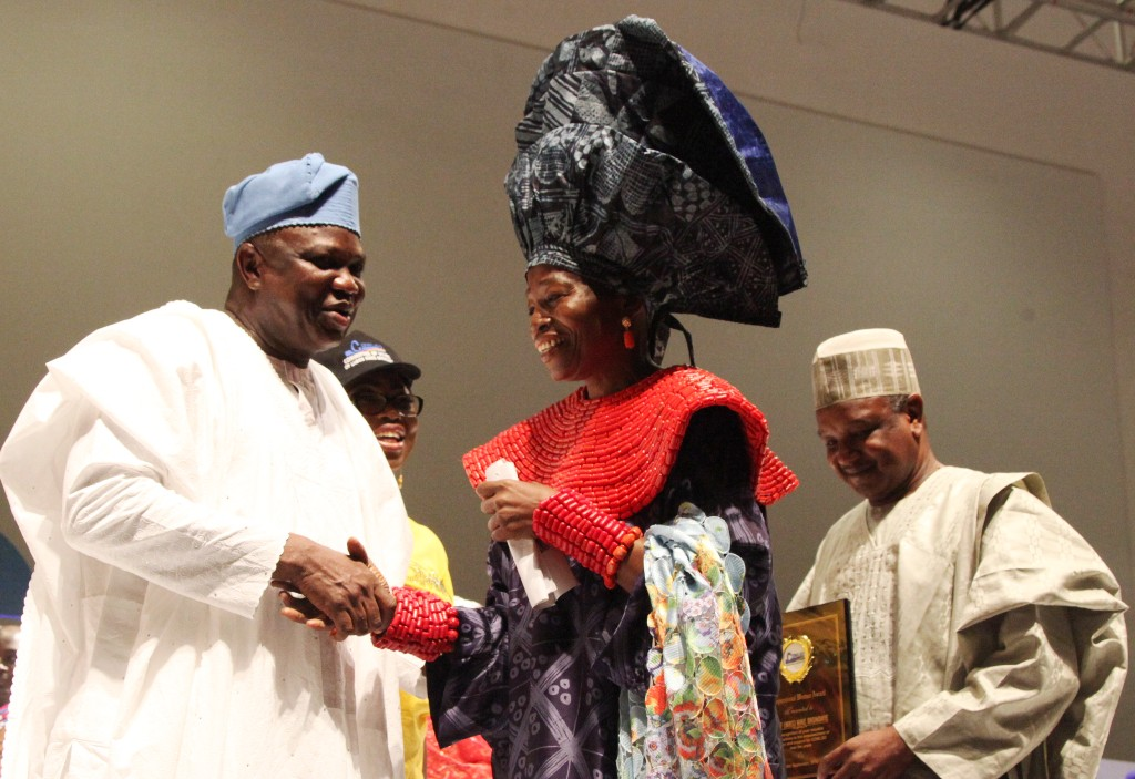Lagos State Governor, Mr. Akinwunmi Ambode (left) congratulating Winner of the Inspiration Woman of the Year Award, C.E.O, Nike Art Foundation, Chief (Mrs.) Nike Okundaye (2nd right) while Chairman, Committee of Wives of Lagos State Officials (COWLSO), Mrs. Bolanle Ambode (2nd left) and Kebbi State Governor, Alhaji Atiku Bagudu (right) watch with admiration during the opening ceremony of the annual National Women Conference organized by COWLSO, at the Convention Centre, Eko Hotels & Suite on Wednesday, September 16, 2015.