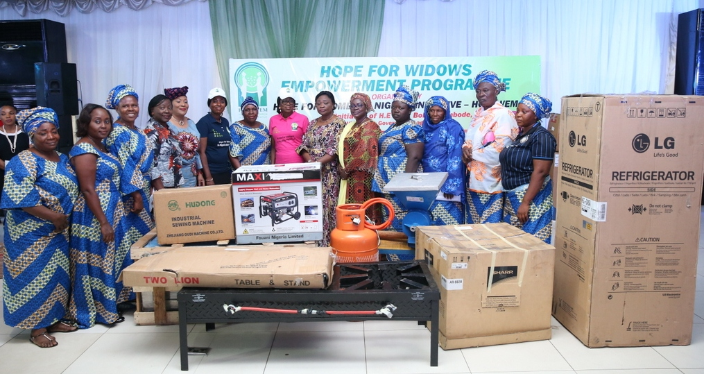Founder, Hope for Women in Nigeria Initiative (HOFOWEM) and Wife of Lagos State Governor, Mrs. Bolanle, (7th right); CEO, HOFOWEM, Ms. Oyefunke Adeleke (6th left); APC Southwest Women Leader, Chief (Mrs.) Kemi Nelson (5th left); Head of Service, Mrs. Olabowale Ademola (4th left); Commissioner for Women Affairs & Poverty Alleviation, Hon. Lola Akande (6th right); Acting Commissioner for Tourism, Arts & Culture, Hon. Adebimpe Akinsola (5th right) with some beneficiaries and their empowerment tools during the Hope For Widows Empowerment Programme for 103 beneficiaries to celebrate the 2017 International Widow's Day, at the Excel Events Centre, Oregun, Ikeja, Lagos, on Thursday, June 29, 2017.