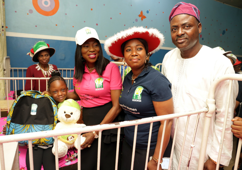 Wife of the Governor of Lagos State & founder, Hope for Women in Nigeria Initiative (HOFOWEM), Mrs Bolanle Ambode (m) supported by CEO. HOFOWEM, Ms. Oyefunke Adeleke (2nd right); and MD. Massey Street Children's Hospital, Lagos, Dr. Olugbenga Aina  (r), to present Xmas gifts to Miss Zainab Kotun (2nd left), during the distribution of various gift items to more than 500 children at Massey Hospital and Sought After Orphanage Home, Langbassa, Ajah, by HOFOWEM, tagged: 'Love at Christmas', at Massey Street Children's Hospital, Lagos, on Monday, 25th December, 2017.