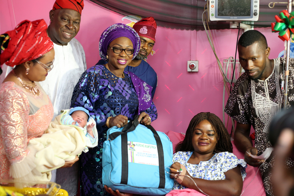 Wife of the Governor of Lagos State, Mrs Bolanle Ambode (3rd left), supported by SA. on Primary Healthcare, Dr. Olufemi Onanuga (2nd left); federal Commissioner, National Population Commission, Barr. Bimbola Saliu-Hundeyin (L); and Hon. Segun Olulade (3rd right), to present Mum's pack to the first baby of the year and his parent, Mr. & Mrs. Festus Ibhadon, during the presentation of gifts to the first baby of the year, born 12:08am, weigh 3.26kg, at the Gbadaga General Hospital, on Monday, 1st January, 2018.