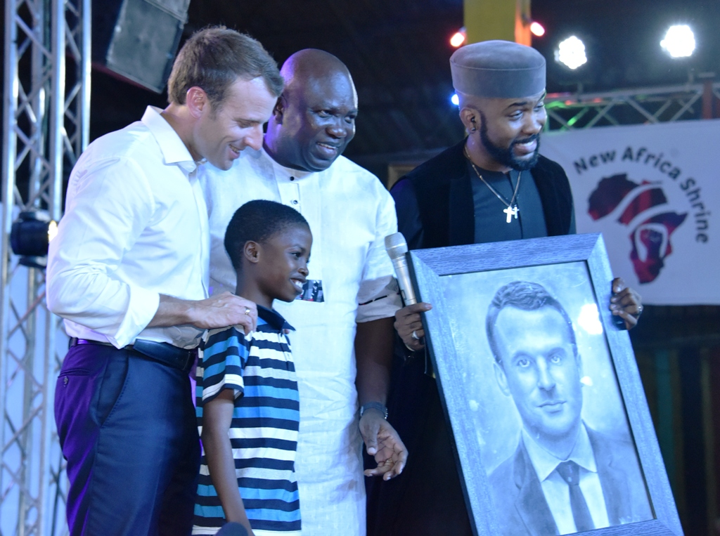 Lagos State Governor, Mr. Akinwunmi Ambode (middle), with President of France, Mr. Emmanuel Macron (left); Nigerian Music Act, Bankole Wellington 'Banky W' (right) when Master Karim Olamilekan presented a painting of the French President during the celebration of African Culture at the Afrika Shrine, Ikeja, Lagos, on Tuesday, July 3, 2018
