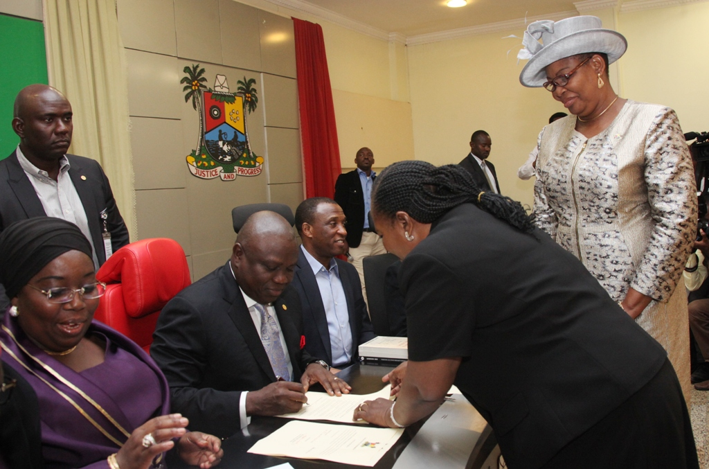 Lagos State Governor, Mr. Akinwunmi Ambode (2nd left) signing the Oath of office of Mrs. Elizebeth Adebunmi Adekanye (2nd right) as Permanent Secretary, Office of Civic Engagement, being conducted by the Director, Legislative Drafting, Ministry of Justice, Mrs. Tola Akinsanya (right) during the swearing-in of the 19 newly appointed Permanent Secretaries at the Banquet Hall, Lagos House, Ikeja, on Wednesday, August 05, 2015. With them are Deputy Governor, Dr. (Mrs.) Oluranti Adebule (left), Secretary to the State Government, Mr. Tunji Bello (3rd left).