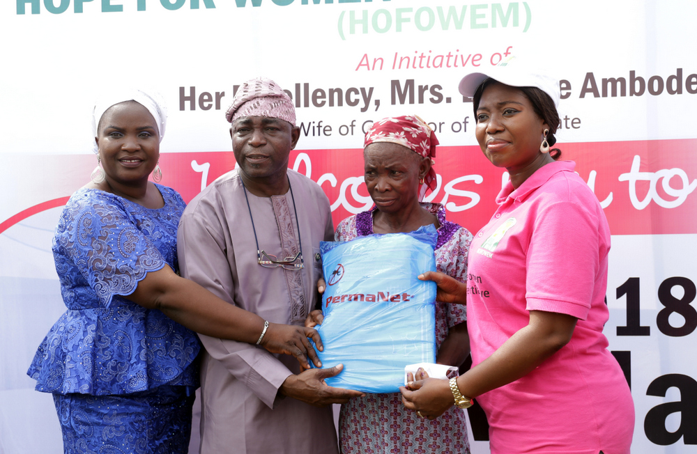 CEO., Hope for Women in Nigeria Initiative (HOFOWEM), Mrs. Oyefunke Olayinka (r); supported by Chairman, Yaba Local Council Development Area (LCDA), Hon. Kayode Omiyale (2nd left) & his wife, Kemi (L), to make symbolic presentation to one of the residents, Mama Janet, when HOFOWEM (a pet project of the wife of the governor of Lagos State, Mrs. Bolanle Ambode) distributed of over 3000 insecticide-treated nets to Makoko residents, as part of activities to mark the 2018 World Malaria Day, at Yaba, on Wednesday, 25th April, 2018.